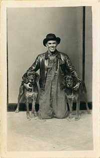 untitled [man in leather jacket kneeling with arms around his two hunting dogs, in front of striped background] by mike disfarmer